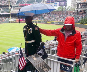 Braves fan holds umbrella over JROTC cadet at rainy baseball game
